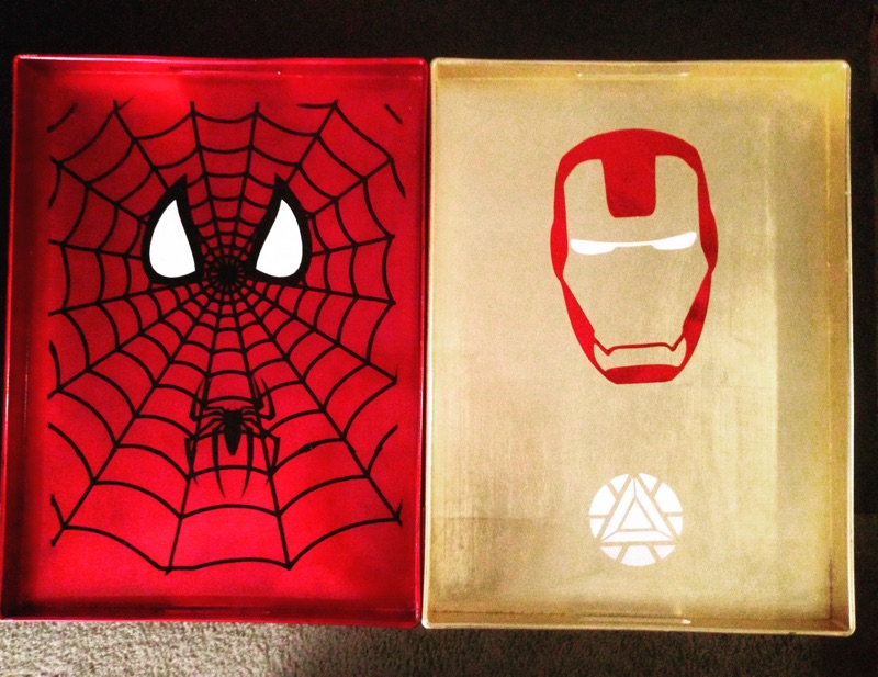 Black Spider-Man Vinyl with Glowing White Eyes on Red Metallic Tray and Red Iron Man Vinyl with White Glowing Eyes on Gold Metallic Tray